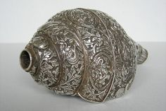 A Tibetan conch trumpet (may have been made in Nepal), made of a shell covered with silver and used to summon monks. This shows its wonderful silver cladding (far better and fuller than on any of some scores we have seen). On the left is the circular hole enabling one to create a powerful sound.