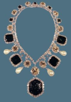 Around her neck, the Empress wore the most splendid diamond and emerald necklace and matching earrings, from the Crown Jewels, ordered at Van Cleef & Arpels for the Coronation, along with the Empress' Crown but made essentially in Teheran by Pierre Arpels. The necklace, mounted in platinum and gold, is composed by an enormous engraved hexagonal emerald, mounted in pendant and surrounded by diamonds of old cut, of four big square emeralds and five smaller ones, (all surrounded by diamonds)