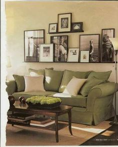 love the layers of photographs, the green couch, and the coffee table.