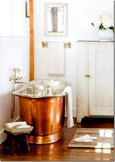 copper soaking tub, natural light, humble details - and the added suggestion of a fireplace/wood stove.