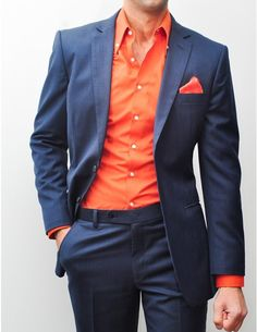 Navy suit with bright reddish-orange shirt and pocket square