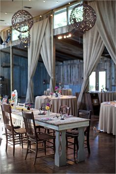 like the burlap draping, rustic chandeliers/lanterns, and casual tables
