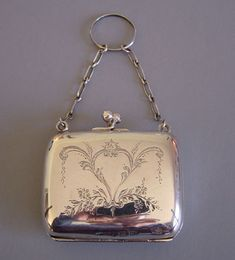 "STERLING silver small purse with scrolls and flowers design both front and back, hallmarked Birmingham 1915 purse, lovely condition with deep green compartments inside, 2-1/3"" by 2-1/3"" by 3/4"" deep with chains 2"" long each leading to a size 11 finger ring. The finger ring is not meant to fit, but to slip loosely over the finger"