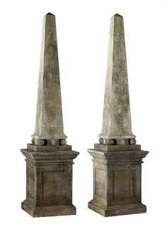 A very tall pair of Continental limestone obelisks, 20th century, of tapering form and square section, each above a panel sided pedestal, 300cm high, 68cm wide