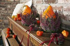 Ein Mantel aus Heide für Kürbisse. Das strahlende Orange wiederholt sich bei dieser Inszenierung in den Lampionfrüchten.