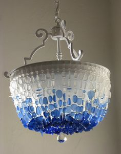 This model: the Nantucket Sound   Serenity meets art in this lovely fixture, like a captured bit of coastal autumn sky.  Sea glass in crisp blues and whites drape elegantly on this lovely ocean-themed chandelier. Looping strands of frosted sea glass in fresh nautical colors of frost white, light sapphire, royal blue and cobalt are accented with tiny clear glass beads, like drops of water. A real focal statement in your coastal decor!  This fixture can be chain hung as a chandelier or mounted…