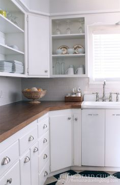 flat front cabinets without profiles can be made to look good with lots of handles details- go with black or dark brass colour for cup handles and edged knobs and the open shelving and the wood tops lift it too...