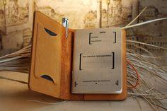 Mini-записная книжка, являющейся также обложкой для паспорта. Её обложка выполнена из натуральной кожи, бережно вырезанной из шкуры, отшлифованной по краю и подготовленной к использованию. Цвета кожи: чёрная, коричневая, рыжая, бежево-серая. Внутренний сменный блок нелинованный или в клетку. Фиксирующая в закрытом положении книжку резинка. Внутри обложки находится карман для визитных, дисконтных или кредитных карт, отдел для паспорта, отдел для размещения внутреннего сменного бумажного…