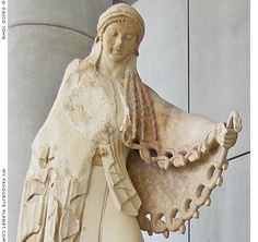 Archaic statue of Athena using her snaky aegis as a weapon in battle against the Giants.  From a statue group depicting the Gigantomachy (the battle between the Olympian gods and the Giants) from the east pediment of the Old Temple of Athena, on the Athens Acropolis, circa 525 BC. This scene, as depicted in other Greek art objects shows the goddess, holding a spear in her right hand, defeating the Titan Encelados (see image below).  Reconstructed statue in the Acropolis Museum, Athens.