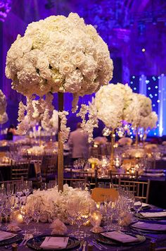 A cluster of white roses and hydrangeas drip with flower petals and stem from a base surrounded by fresh blooms.
