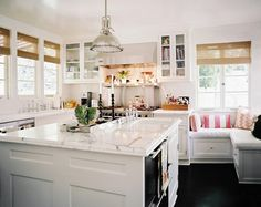 Kitchen Photo - An open white kitchen with a center island and a corner bench, design by Jennifer Dyer