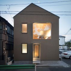 This compact Japanese home is set on the end bay of a housing estate, at the intersection of two roads. The home's exposed position and small site lead the