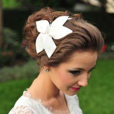 Se você é uma noiva romântica que sonha em casar usando tiaras ou coroas de flores nos cabelos, a tiara com flor de tecido é o arranjo de cabelo ideal para completar seu visual.  Foto: Laura Alzueta www.mercedesalzueta.com.br