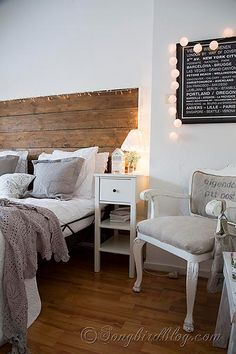 Grey and white bed linens contrast with repurposed wood headboard.