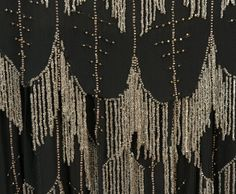 DAIR PARIS CHIFFON FLAPPER DRESS with BEADED FRINGE, 1920s. Black silk with crystal fringe forming an allover scallop pattern with vertical bands of clear and silver beads, blouson top and chiffon underdress. Labeled. Detail
