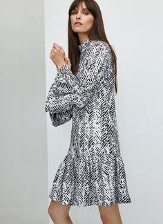 Vestido en mezcla de poliester y elastano con estampado abstracto bicolor: blanco y negro. Corte recto, cuello perkins y detalle de volantes en puños y bajo.
