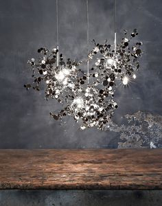 Argent pendant light by Terzani is a magical lamp that reflects light irregular bright reflection the walls thanks to the small silver coins. The pendant light seems to float like a bright cloud that disperses in the air.