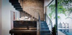"""קיר זכוכית בצורת האות ר' מפריד בין הבריכה לסלון ולגרם המדרגות, שעשויות פלדה מכופפת בעובי 12 מ""""מ ושנתלו על קיר לבנים ( צילום: איתי סיקולסקי )..."""