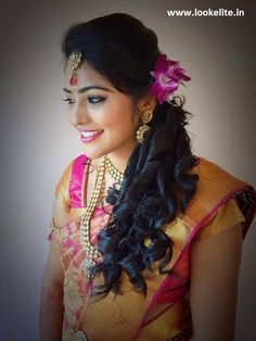 Traditional Southern Indian bride wearing bridal hair, saree and jewellery. Reception look.