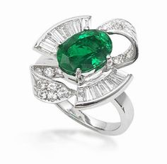 An emerald and diamond ring. The oval mixed-cut emerald, within a tapered baguette-cut diamond semi-surround, to scrolling bows set with brilliant-cut diamonds, mounted in white gold. Emerald Jewelry, Gemstone Jewelry, Beaded Jewelry, Jewelry Box, Jewelry Rings, Jewelry Accessories, Fine Jewelry, Jewellery, Mom Ring
