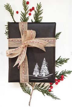 Rustic Christmas gift wrap idea - plain black wrapping paper with hand stamped holiday image, finished with hessian ribbon and bakers twine
