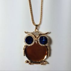 """gold crystal owl pendant necklace •gold crystal owl pendant necklace. has a gold body, gold detail, and gold chain. has blue crystal eyes.   •I have one blue owl, and one gold owl in stock.   •chain is 31"""" long. and the pendant is 2"""" high and 1,5"""" wide.   •new never used  •no trades  •not from listed brand Urban Outfitters Jewelry Necklaces"""