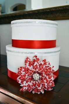 Beautiful lace covered wedding card box with bling detail and a red patterned flower.