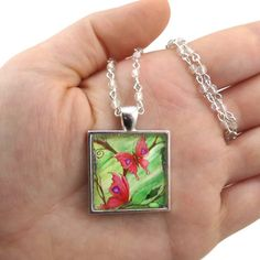 """Do you welcome butterflies in your garden? Say hello to """"Butterfly Love"""". These beautiful pink butterflies have purple hearts on their wings and are flying amongst purple wisteria flowers – all against a bright green background. Fantasy Art Pendants by KK Swann allow you to feed your whimsy wherever you go. Inspire your lively and visionary spirit with this necklace featuring Drakey Art's original painting """"Butterfly Love"""". Customizable to fit your personal style, choose your..."""