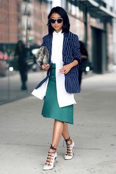 Street style look com camisa branca, blazer listrado, saia verde e sandália amarração.