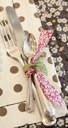 I really like the simplicity of cutlery tied together with a ribbon or rafia or something organic.