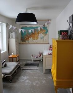 Concrete floors, rolling pallet and yellow armoire make this child's room striking.