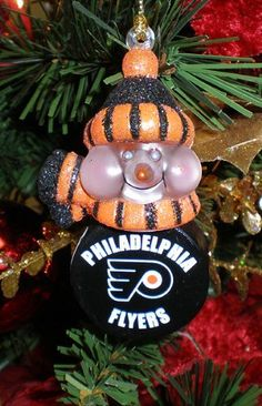 """NHL Philadelphia Flyers LED Lighted Hockey Puck Snowmen Christmas Ornament by Scottish Christmas. $8.99. Philadelphia Flyers Christmas OrnamentsItem #21266Officially licensed merchandiseSnowmen feature a light-up head and a scarf emblazoned with official team colors and team logoThe puck body displays your favorite NHL teams logoAdditional product features:Light-up with an LED lightOrnaments come ready-to-hang on a gold cordFully dimensionalDimensions: 3""""Material(s): acrylic"""
