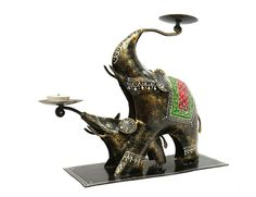 Intricately carved with the smaller elephant emerging from the front legs of the bigger one. White embossed work and multicoloured carvings on them accords an ethnic look. This Two Elephant Tea Light Holder set makes an ideal pair for decoration.