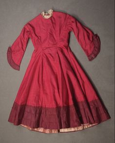 Circa 1868 Girl's Taffeta, Organdy, Lace, and Velvet Ribbon dark red-wine dress with rhinestone buttons. Via Fine Arts Museums of San Francisco.
