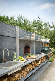 WWOO high, anthracite, outdoor kitchen with a stainless steel sink including a fire-plug, a pizzaoven and a Big Green Egg.