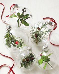 Create your own festive decoration by filling glass ornaments with sprigs of holly, bayberry, and evergreens.