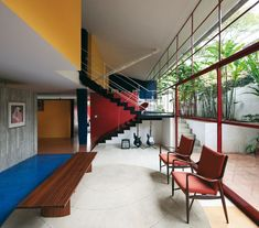The Baeta  home's study is partially below ground. Vilanova Artigas softened the brutality  of the compact, solid forms in reinforced  concrete through the use of primary colours:  red, white, blue, yellow and black. In this way,  he established a kind of hierarchy between  the different elements of the building.  The concrete stairs, for example, are painted  black