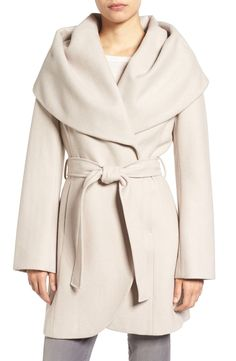 A shoulder-draping shawl collar brings face-framing drama to a warm wool-blend wrap coat in a versatile length with a graceful cutaway hem.