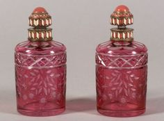 Pair of Continental Enamel Accented, Cranberry Flashed, Cut to Clear Glass Colognes, first quarter 20th century, cylindrical bottles cut with floral swags, with pink enameled domed lid with basse taille pyramid and arrow borders, and matching enameled neck band to body, ht. 6 in.