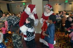 Santa and Mrs. Claus greet children at the CU System Staff Council reception for families from Aurora's Buckley Air Force Base #CUHSLibrary