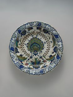 This dish shows a cusped edge drawn from a Ming prototype. The wave, foam and rock design of the rim recall its Chinese model as well. Unusual coloration of sage-green and manganese purple are combined with more typical Iznik tones such as blue and turquoise