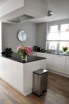gray walls, light wood floors, white cabinets, dark counter tops
