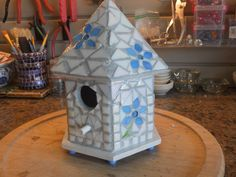 White, six-sided with blue flowers and light almost blue grout birdhouse
