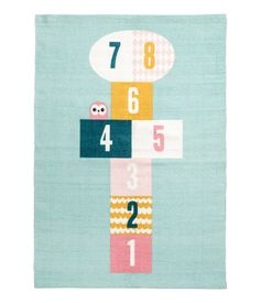Turquoise. Rectangular cotton rug with a printed hopscotch motif at front and non-slip backing.