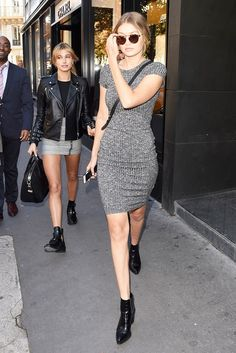 Gigi Hadid wears a ribbed gray sweaterdress, round sunglasses, and black ankle boots