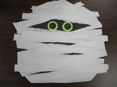 How to Make a Spooky Mummy Face  Cut a black square 12 * 12  Tear strips of white paper - make sure to tear it the down the width (shorter) not the length (longer).  It does not tear very well if you tear it on the longer length!  Punch out black and bright Halloween colors for the eyes.     Have the students cut the square into a circle and glue every thing together.