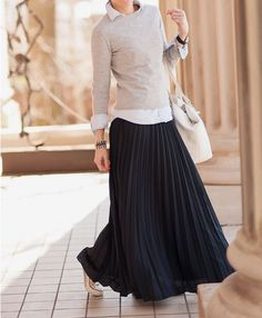 Black pleated maxi skirt, grey sweater, blue shirt, and sneaker