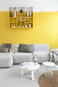 salon avec mur double couleur blanc et jaune, canapé gris, tapis rond en rotin