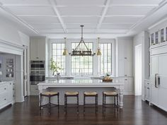 White kitchen with large windows, antique light fixture and Taj Mahal Quartzite island countertop. Architecture and interior design by Christopher Architecture & Interiors. Photography by Chris Luker of Luker Photography.