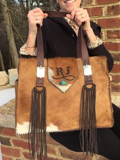 The Buckaroo Diaper Tote with side pockets lined in suede, straps with rectangle conchos and D loop fringe, and the owners daughter's initials on the flap with a turquoise stone.   gowestdesigns.us